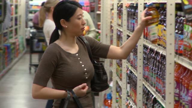 MS PAN SELECTIVE FOCUS Woman choosing juice shopping in supermarket, Richmond,  Virginia, USA