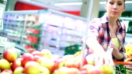 Woman choosing some apples in supermarket.