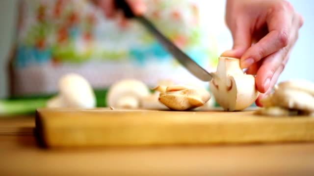 Frau Hacken Pilze mit Messer auf Schneidebrett.