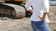 woman civil engineer and tractor car in construction site