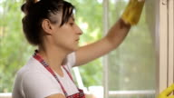 Woman cleaning a glass on the window