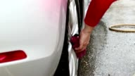 MS Woman cleaning alloy wheels on her car