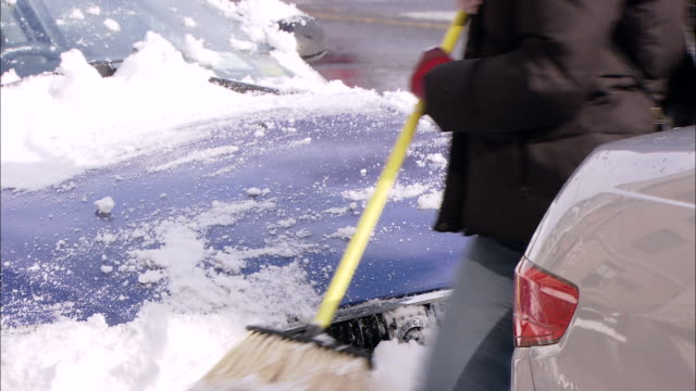MS ZI PAN TU Woman cleaning off snow from car on Central Park West / New York, New York, United States