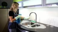Frau reinigt Spülbecken