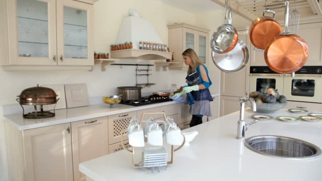 Woman cleans the cooker in kitchen