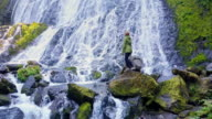 Woman Climbing Over Rocks at Foot of Waterfall