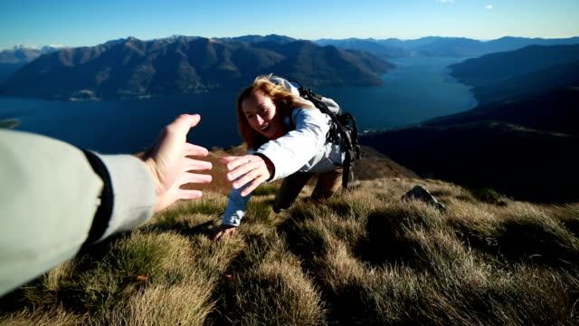 Woman climbs mountain range, hand reach out to help