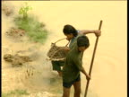 Woman collects mud from river as man gathers silt following monsoon flood Cambodia