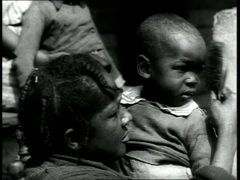 1939 CU woman combs child's hair, other children sitting behind them / Charleston, South Carolina