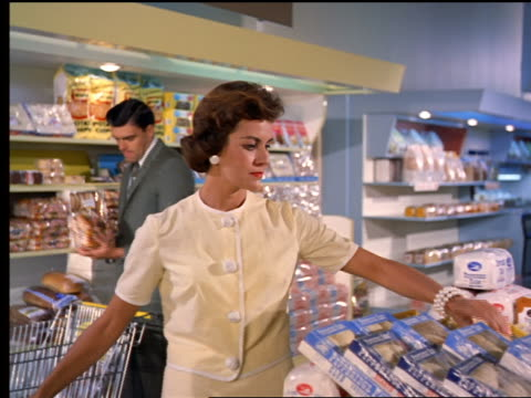 1962 MS woman comparing two different types of rolls in grocery store with man shopping in background