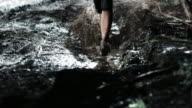 TD Woman competing in a night trail run running across a puddle