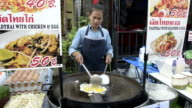 A woman cook fried egg in a food stall