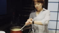 Woman Cooking and Checking Time