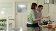 Woman cooking and husband tasting food