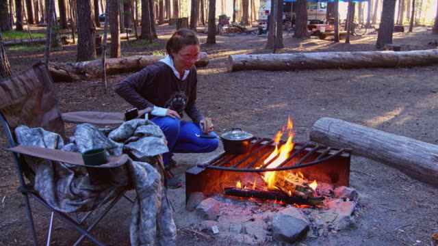 Woman Cooking Breakfast on Fire in Woodland Campsite