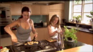 Woman cooking dumplings as daughter picks leaves off basil plant and minces leaves