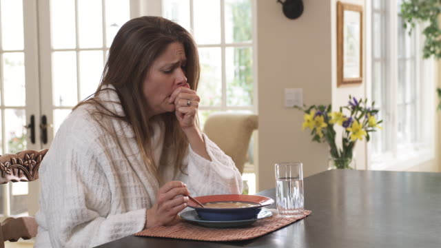 MS Woman coughing , sitting at dining table having bowl of soup, Phoenix, Arizona, USA