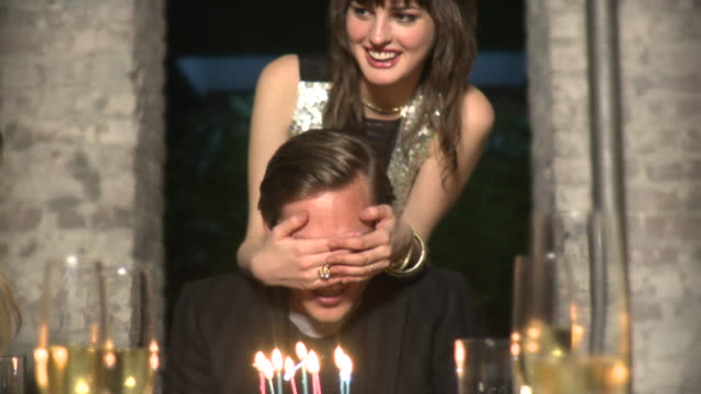 MS Woman covering man's eyes, man blowing candles on birthday cake, New York City, New York, USA