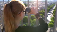 Woman creating memories by taking pictures of Paris from top of Arc de Triomphe