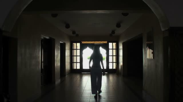 Woman (silhouette) crossing a dark arabian hall towards sunny exterior