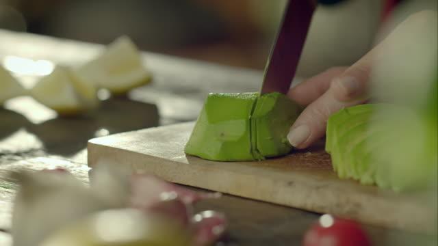 Woman cutting avocado into slices