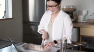 Woman cutting baguette in kitchen
