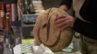 CU ZO MS Woman cutting bread in delicatessen / Beaune, Burgundy, France