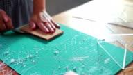 Woman cutting pattern on acrylic sheet