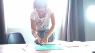 Woman cutting pattern on acrylic sheet with Plastic Cutting Tools.