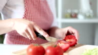 HD: Woman cutting tomato