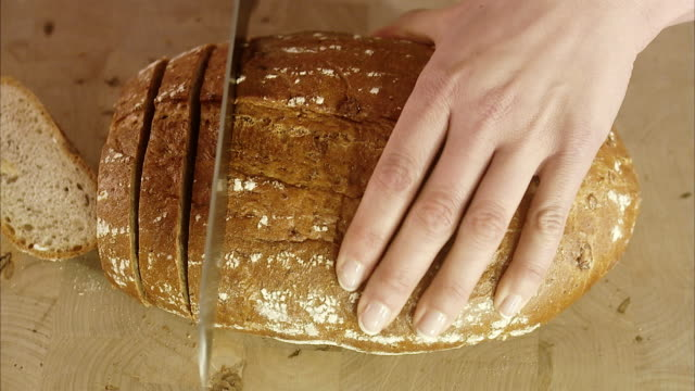 Woman cutting up bread, Sweden.