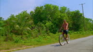 A woman cycles past a shack. Available in HD.