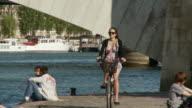 MS Woman cycling towards camera along Seine River, Port de la Turnelle, Paris, France