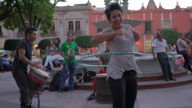 Woman dances w/hoop in park with street band