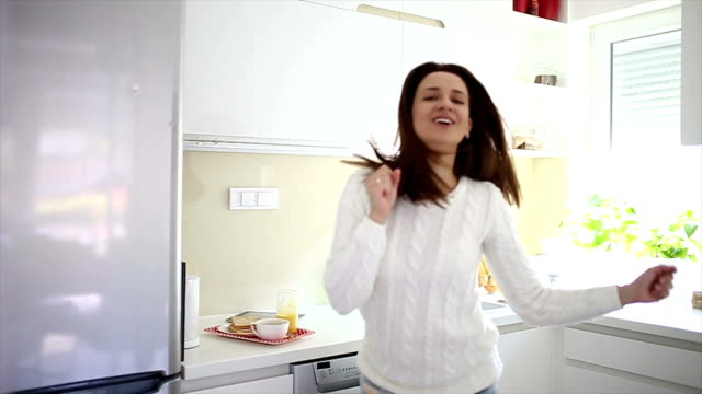 Woman dancing at home and singing