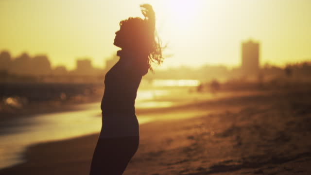 woman dancing at the beach at sunset