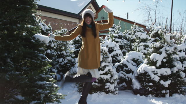 woman dancing in a snowy grove of Christmas trees