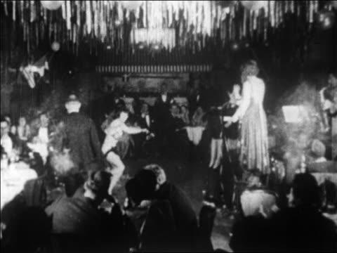 B/W 1928 woman dancing in nightclub floor show as audience watches / newsreel