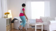 woman dancing then falling back into chair and kicking of shoes