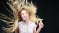 MS Woman dancing wearing earphones, long blond hair moving in wind / London, Greater London, United Kingdom