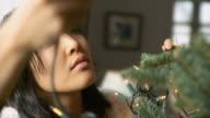CU Woman decorating Christmas tree with fairy lights / New York City, New York, USA