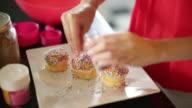 CU woman decorating cupcakes.