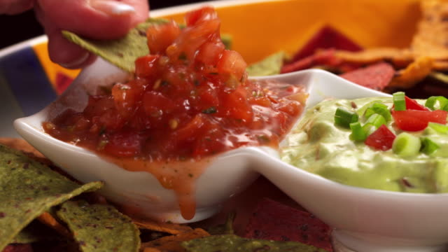 A woman dips tortilla chips into a variety of salsas on a Mexican appetizer platter.