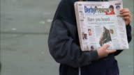 A woman displays the front page of the Derby Preview newspaper. Available in HD.