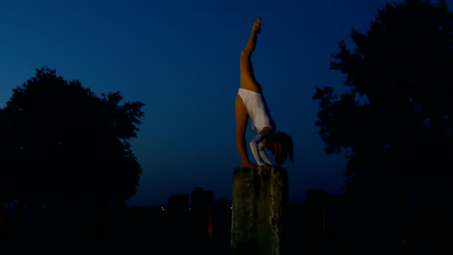 Woman does handstand and twine on concrete column