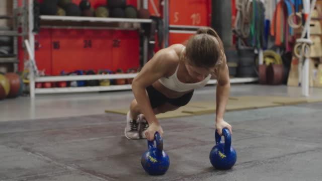 Woman doing kettlebell push-ups