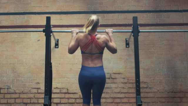 Woman doing pull-ups in gym