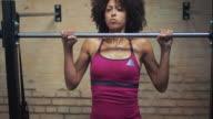 Vrouw doet pull-ups in sportschool