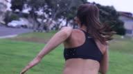 A woman doing sprints up a grass hill.