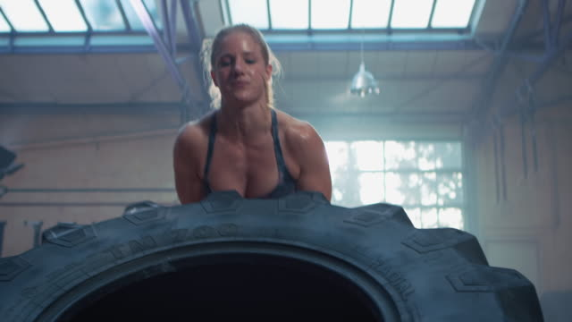 Woman doing workout with big tire